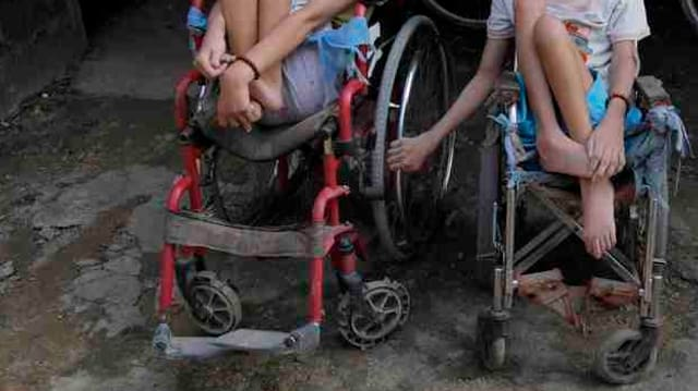 Zwei behinderte Kinder in Rollstühlen.