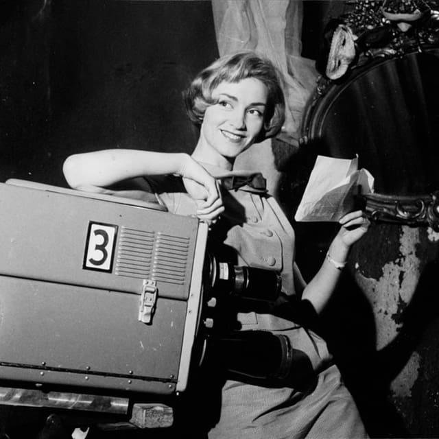 Heidi Abel lehnt mit einem Arm auf einer Fernsehkamera.