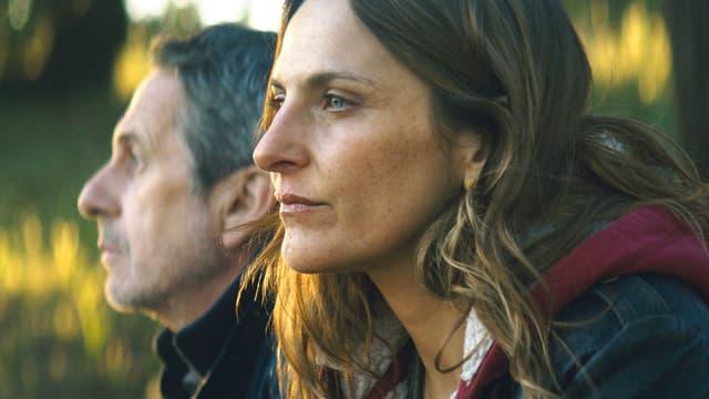Eine Frau und ein Mann sitzen nebeneinander und blicken beide in die Ferne.