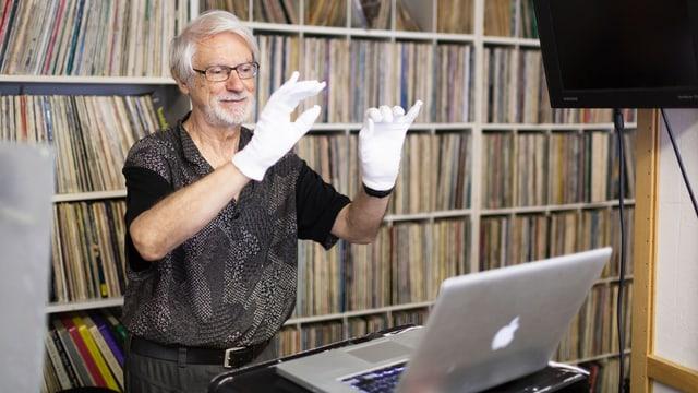 Bruno Spoerri trägt weisse Handschuhe. Er steht vor einem Bücherregal und hinter einem Laptop.