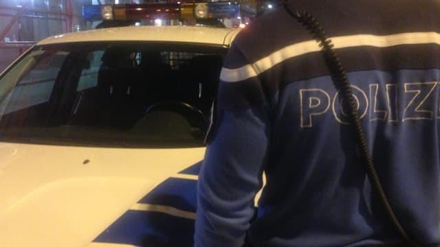 Ein Oltner Stadtpolizist vor einem Polizeiauto.