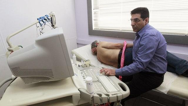 Arzt sitzt an medizinischem Gerät und untersucht einen Patienten.