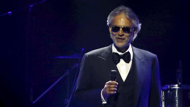 Andrea Bocelli im dunklen Anzug auf der Bühne.