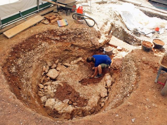 Archäologin arbeitet in runder Öffnung im Boden