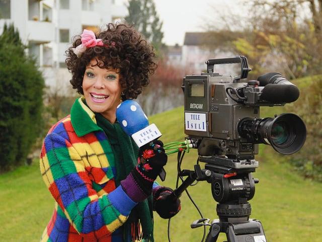 Frau Schruppatelli als Reporterin mit Kamera und Mikrofon