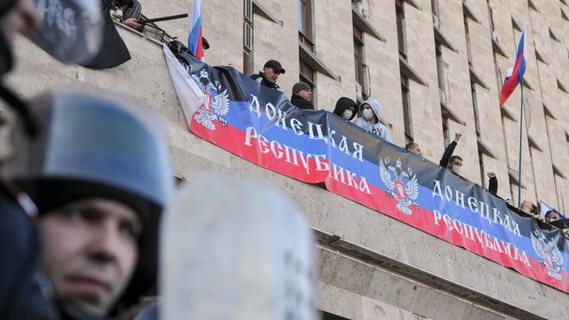 Vermummte Menschen mit russischen Flaggen auf einem Balkon.