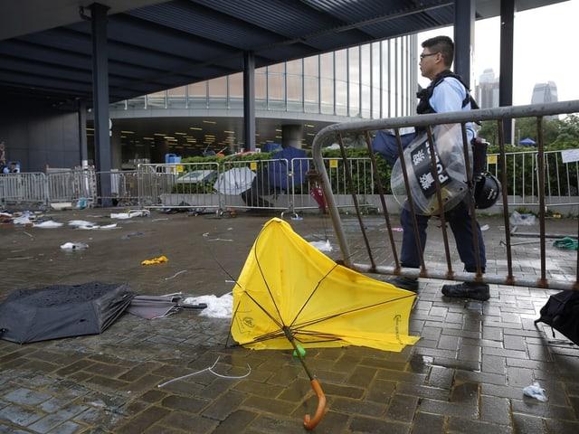 Kaputte Regenschirme, ein Polizist