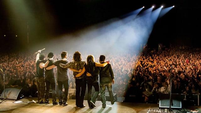 Blick von Hinten auf Sechs Männer, die an einem Bühnenrand stehen und auf ein grosses Publikum schauen.