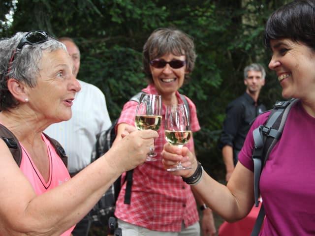 Drei Wanderinnen stossen mit einem Glas Wein auf das Erreichen des Ziels an.