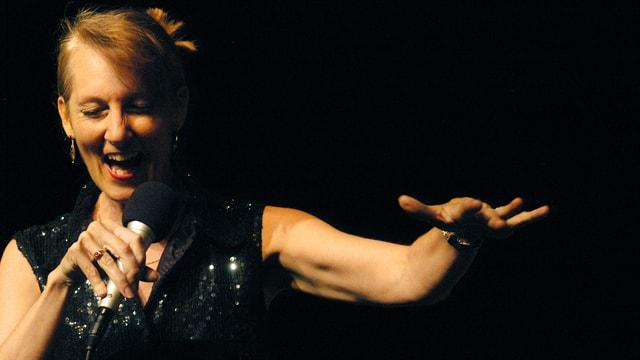 Die Sängerin Lauren Newton singt in ein Mikrofon.
