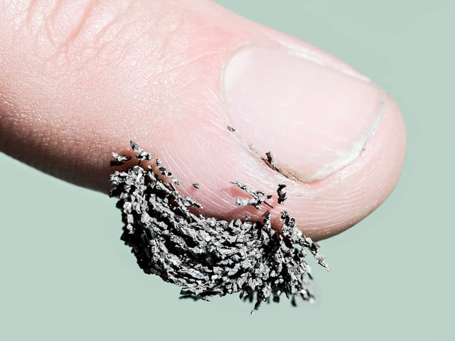 Eine Fingerkuppe, an der kleine Metallsplitter hängen.