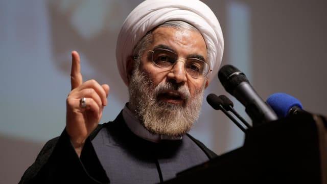Rohani spricht mit weissem Turban und erhobenem Finger in ein Mikrofon.
