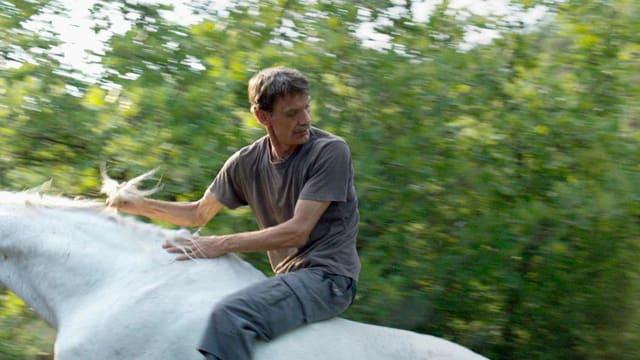 Ein Mann sitzt ohne Sattel auf einem Pferd.