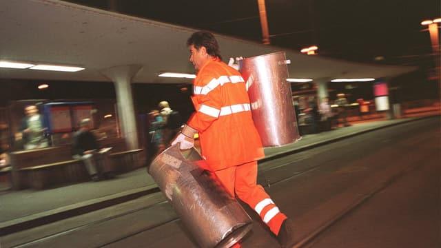 Ein Strassenwischer bei Nacht, der in jeder Hand einen Abfalleimer trägt.