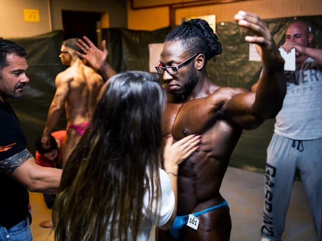 Bodybuilder hält die Arme hoch. Eine Frau tastet seine Muskeln ab.