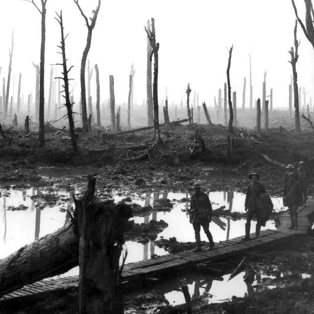 Soldaten marschieren durch einen zerbombten Wald.