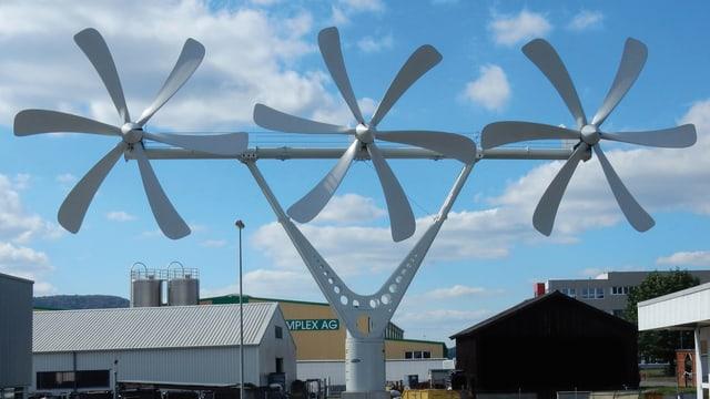 Drei sechsflüglige Rotoren nebeneinander an einer Stange montiert vor blauem Himmel