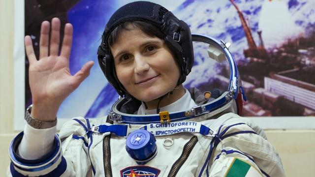 Samantha Cristoforetti winkt im Raumanzug ohne Helm