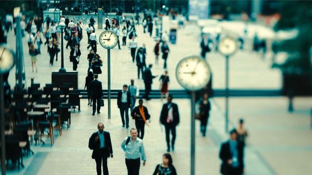 Passanten in London, alle paar Meter steht eine Uhr.