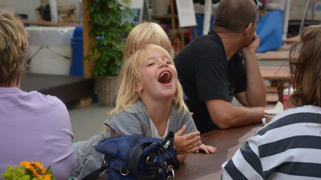 Kleines Mädchen, dass ausgelassen lacht.