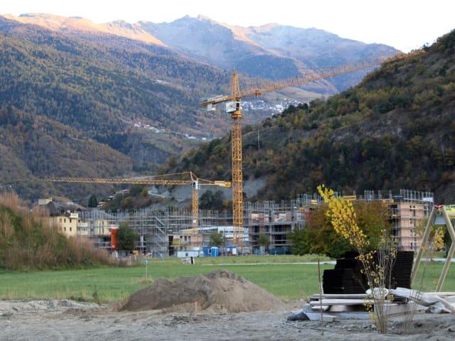 Baustelle, Bergpanorama im Hintergrund.