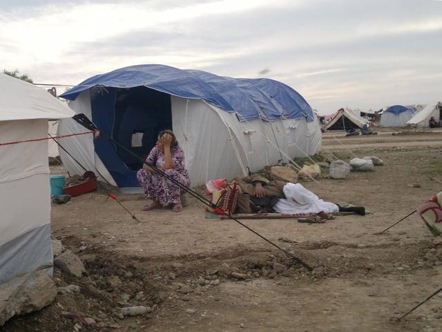 Eine Flüchtlingsfrau sitzt vor ihrem Zelt im Lager Khanke. Daneben liegt ein Mann auf einer Matte.
