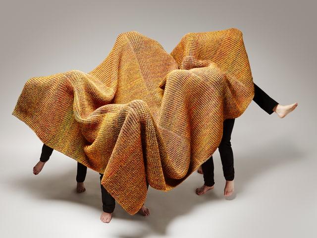 Gruppe von Menschen mit einem Teppich überdeckt, nur Beine sichtbar