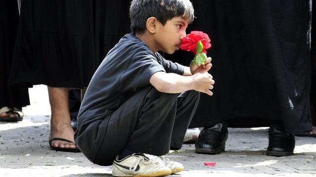 Ein tamilischer Junge in den Kniene mit einer Nelke in der Hand.