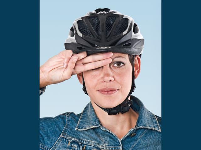 Eine Frau trägt einen Velohelm und hält zwei Finger zwischen Nasenwurzel und Helmkante.