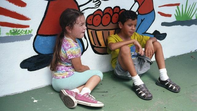 Zwei Kinder sitzen an eine Wand gelehnt am Boden.