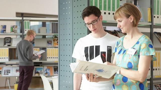 Eine Berufsberaterin zeigt einem Schüler eine Broschüre.