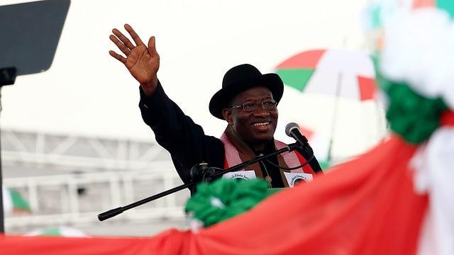 Jonathan Goodluck steht an einem Mikrofon und Winkt, er trägt schwarze Kleidung und einen Hut