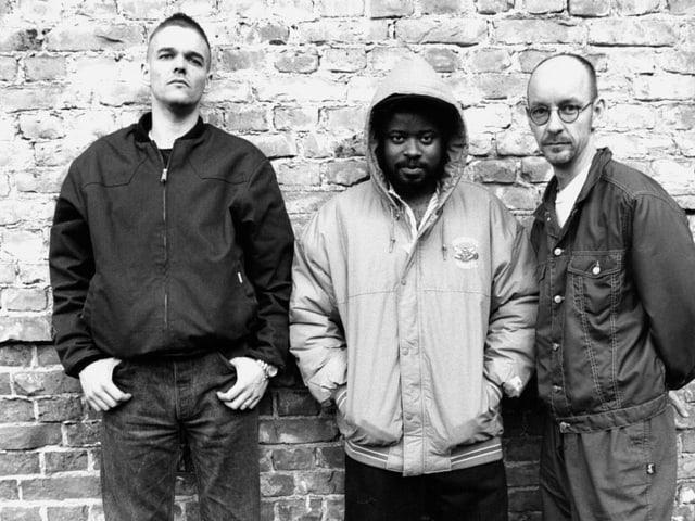 Schwarzweissfoto: Drei Männer stehen nebeneinander vor einer Mauer.