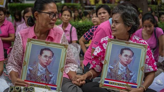 Thailänderinnen tragen gerahmte Bilder des Königs.
