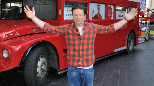 Jamie Oliver in Siegerpose vor einem roten Doppelstöcker-Bus.