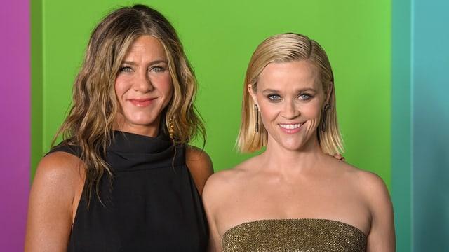 Jennifer Aniston und Reese Witherspoon schauen in die Kamera eines Fotografen.