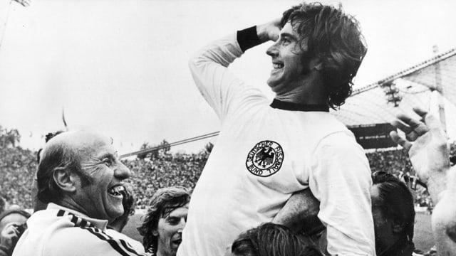 Gerd Müller im Jahr 1974, wie er nach dem siegbringenden Tor von Trainer und Mannschaftskollegen hochgehoben wird.
