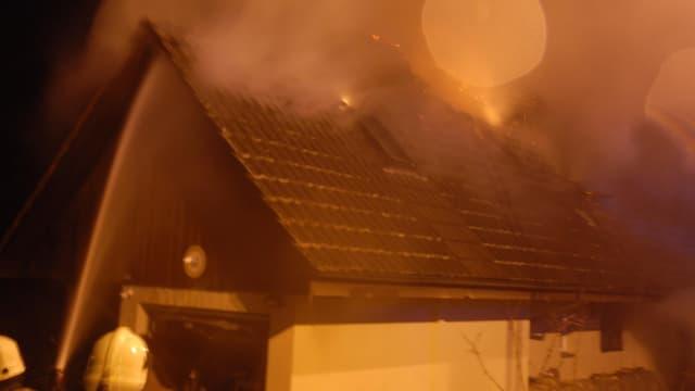 Feuerwehrmänner spritzen Wasser auf ein brennendes Hausdach.