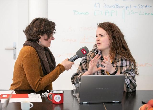 Frau interviewt andere junge Frau mit Mikrofon. Davor steht ein Laptop.