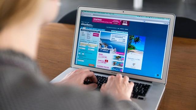 Blick über die Schulter einer Frau auf den Bildschirm eines Laptops auf einem Tisch.