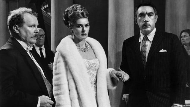 zwei Männer im Anzug und eine Frau im weissen Pelzmantel