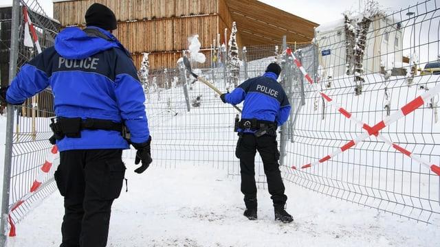 Zwei Polizisten räumen in Davos Schnee weg.