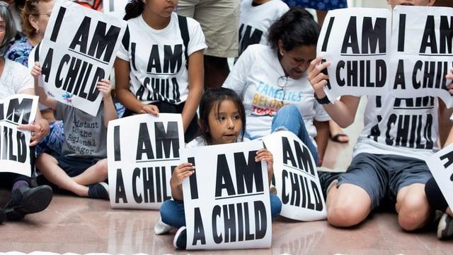 Ein Kind mit einem Schild «I am a child»