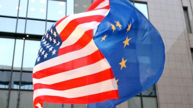 Symbolbild: Eine US- und eine EU-Fahne wehen im Wind.