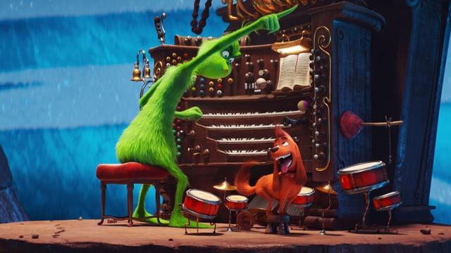 Ein haariges Monster sitzt an einer grossen Orgel. Es schaut grimmig auf einen kleinen Hund zu seinen Füssen und zeigt mit dem Finger nach rechts. Der Hund schaut freudig zu ihm hoch.