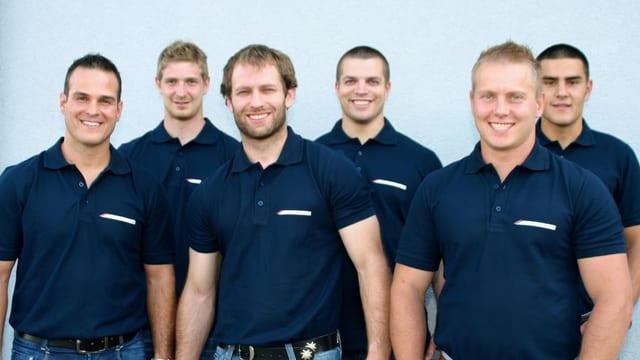 Die sechs Teammitglieder stehen alle nebeneinander. Sie tragen ein blaues Kurzarm-Kragenshirt