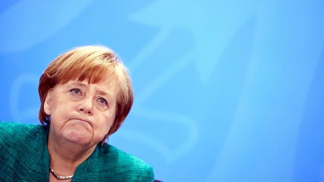 Merkel presst die Lippen zusammen.