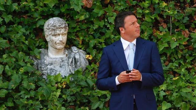 Matteo Renzi steht mit dem Handy in der Hand vor einer hohen Hecke, aus der eine Büste ragt.