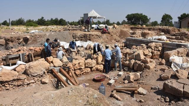 Eine Gruppe von Menschen arbeitet auf einer Ausgrabungsstätte.