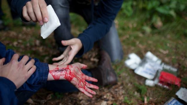 Arm mit Blut, jemand tupft ihn ab.